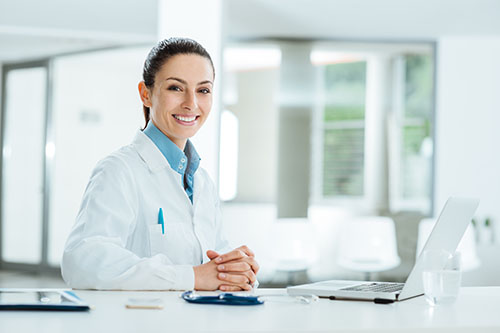 Female doctor working at office desk