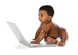 A toddler playing with a laptop computer