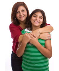Mother standing behind daughter and hugging her.