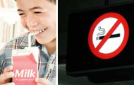 Child drinking milk and smiling and a No Smoking sign