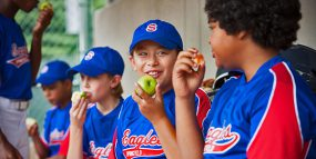 Boys' baseball team eating apples