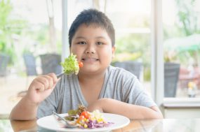 Young boy eating a salad