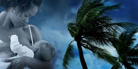 Image of mother breastfeeding her baby over background of palm trees blowing in heavy winds