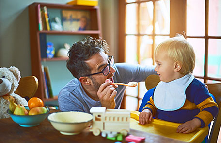 Photo of smiling dad offering toddler a spoonful of oatmeal