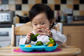 Photo of baby girl in high chair trying broccoli and sweet potatoes for the first time