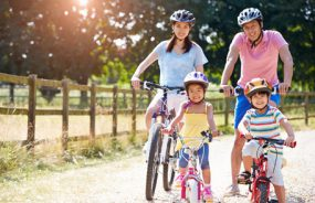 Mother, father, and two children riding bicycles in countryside