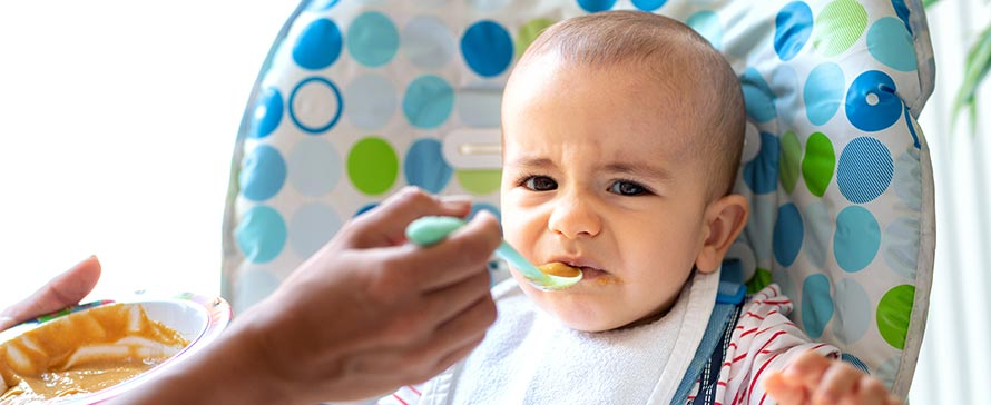 Baby in highchair reacts negatively to baby food