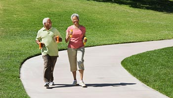 A senior couple walking on a paved trail