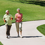 A man and woman walking on a paved trail.