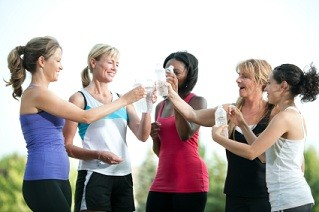 Young women cheers with water bottles after group fitness.