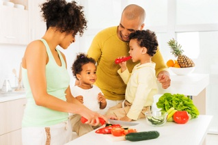 African American family prepares vegetables in kitchen.