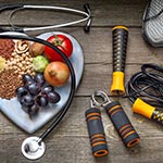 A heart-shaped plate with fruits vegetables, and grains next to exercise equipement