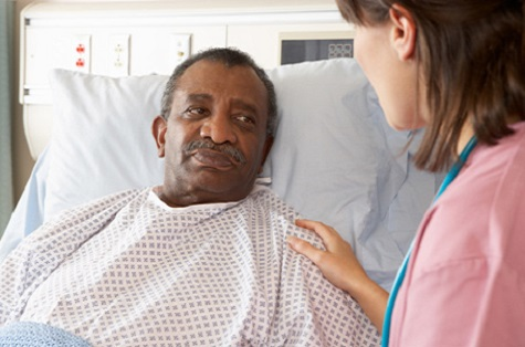 nurse talking to male patient in hospital bed