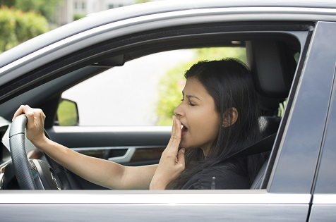 lady driving car and yawning