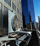 Photo of an outdoor HVAC air conditioner unit located on a high-floor porch of a New York skyscraper.