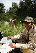 Photo of a uniformed man recording information in the field