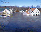 Photo of a flooded neighborhood with water levels covering the bottom of the houses.