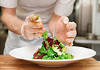 Close up photo of gloved hands preparing a salad.
