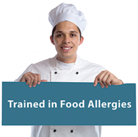 Photo of a chef holding a sign that reads Trained in Food Allergies.