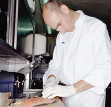 Photo of chef preparing fish filet.