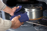 Photo of chef removing pot from oven.