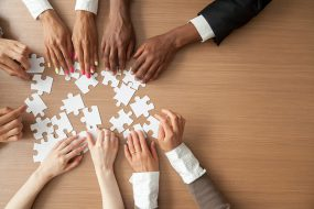 Hands of multi-ethnic team assembling jigsaw puzzle representing teamwork.