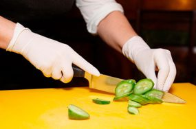 Photo of gloved hands chopping a cucumber.
