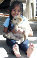 A girl holding her puppy.