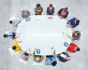 Overview of people meeting at a circular table.