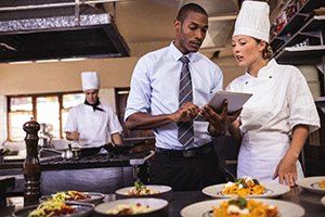 Photograph of a kitchen manager discussing guidelines with a chef.