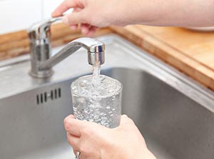 Photo of a woman getting a glass of water from kitchen faucet.