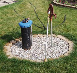Photo of a common household private well in a yard.