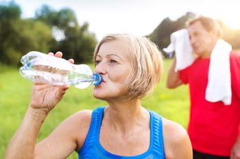 Senior woman drinking from water bottle outdoors with senior man wiping face with towel in background