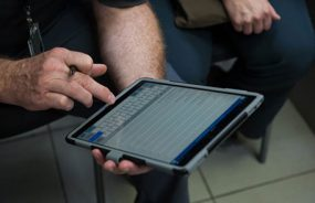 An image of a man entering data on a computer tablet
