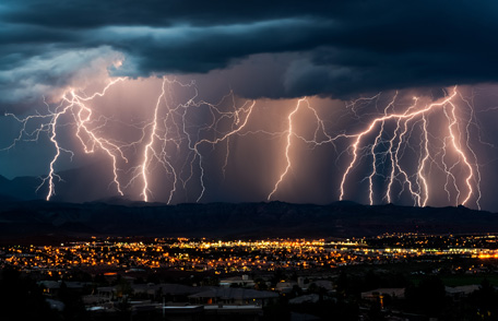 Multiple streaks of lightning touch ground as a large storm passes over a city.