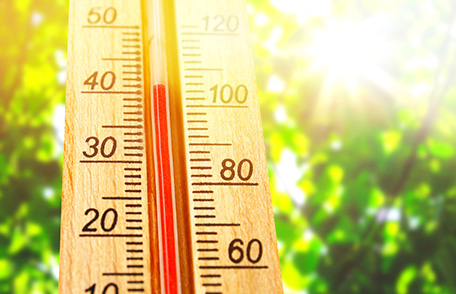 A thermometer in the foreground registering over 100 degrees Fahrenheit with bright blue sky behind it.