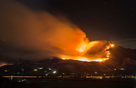 A wildfire rages on the side of a mountain with a town below.