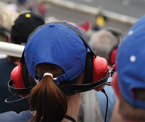 at a car race with noise cancelling headphones