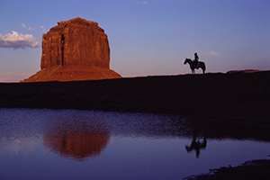 Man on horseback observes towering natural rock monument.