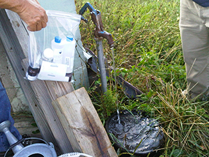 HSB staff gathers water samples from a private well to test for contaminants.