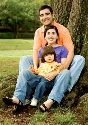 Hispanic family outside sitting in front of a tree