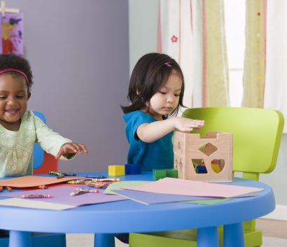 Two children playing at a table with crayons and paper