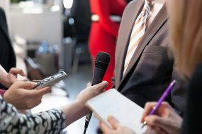 Person being interviewed by a group of reporters