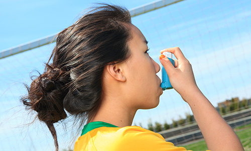 Young girl using asthma inhaler outdoors