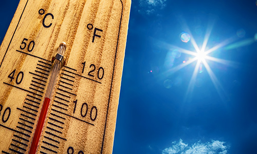a thermometer showing over 100 degree fahrenheit against a bright sunny sky