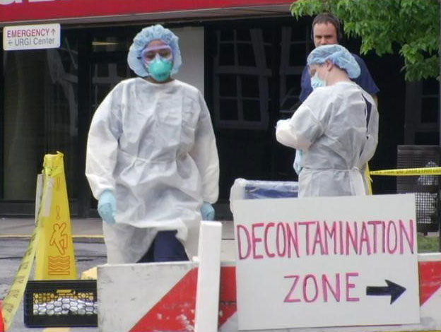 Two people with hazmat suits and masks in a decontamination zone.