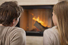 man and woman sitting in front of fireplace with burning logs
