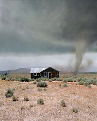 Photo of tornado moving across plains approaching house.