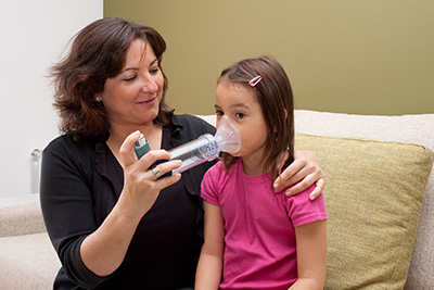 a mother helping her child with an inhaler