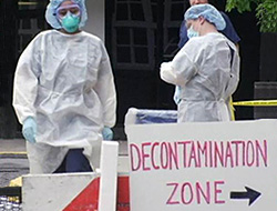 people in hazmat suits standing behind a sign pointing to the decontamination zone